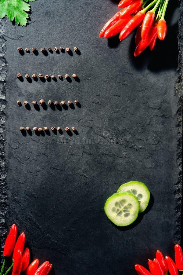 Interi pepe nero, peperoncino e fette di cetriolo fotografie stock libere da diritti