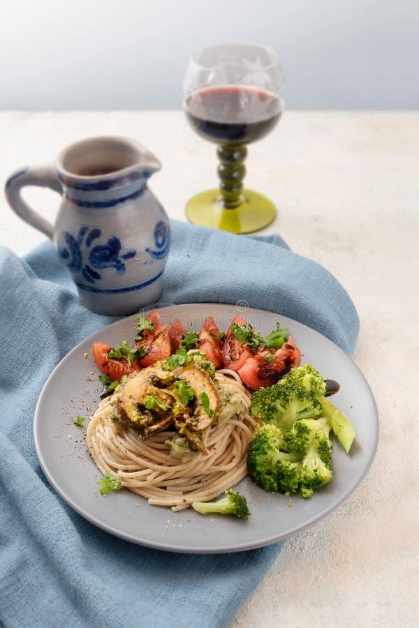 Interi spaghetti del grano con i chamignons, i broccoli, i pomodori e lui fotografia stock