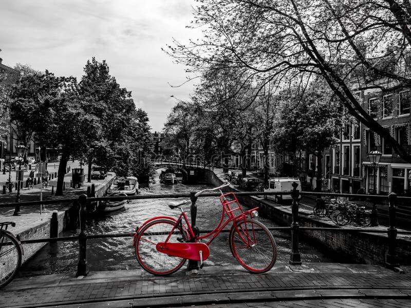 Interim rosso della bicicletta su un ponte, in bianco e nero fotografia stock