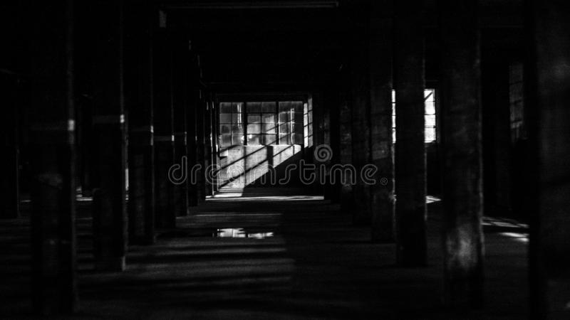 Interior of an abandoned factory shot in black and white. The interior of an abandoned factory shot in black and white stock photo