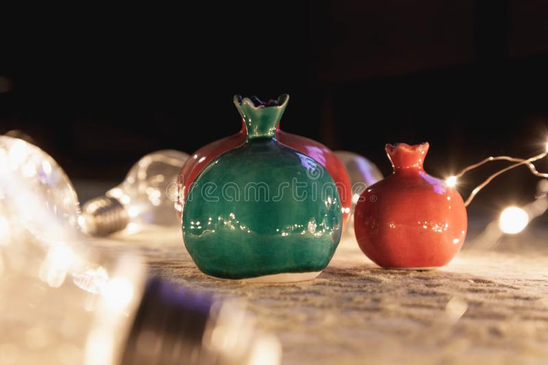 Decorative ceramic Pomegranates colored pots with Light Bulbs on Floor. Interior Accessories | Decorative ceramic Pomegranates colored pots with Light Bulbs on stock images