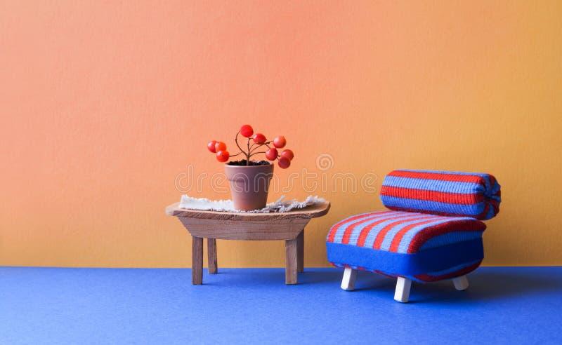Interior acogedor de la sala de estar El sofá de la silla del rojo azul y la tabla de madera con las bayas hermosas plantan el po fotos de archivo libres de regalías