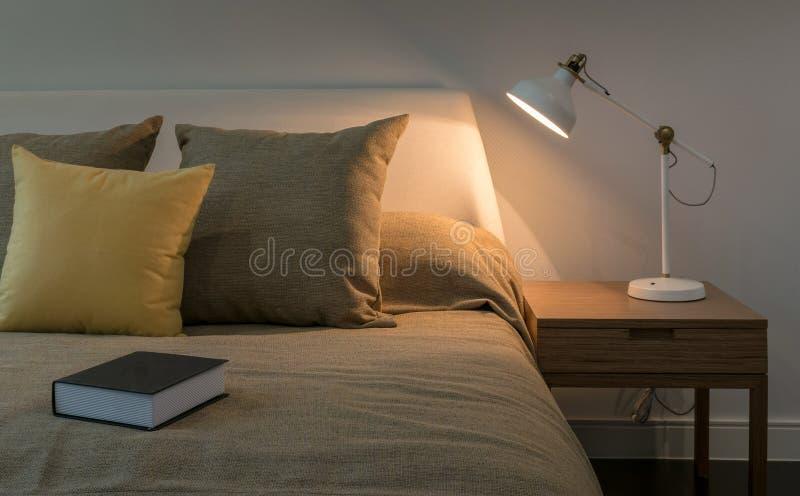 Interior acogedor del dormitorio con el libro y la lámpara de lectura en tabl de la cabecera imagenes de archivo