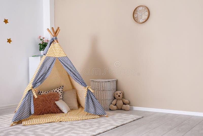 Interior acolhedor da sala das crianças com barraca e brinquedos do jogo imagens de stock