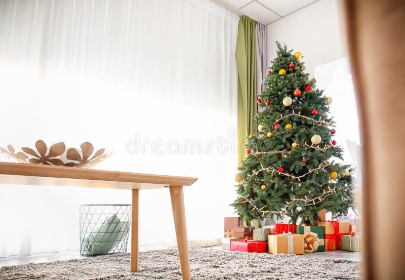 Interior acolhedor da sala de visitas com tabela de madeira e a árvore de Natal bonita imagem de stock