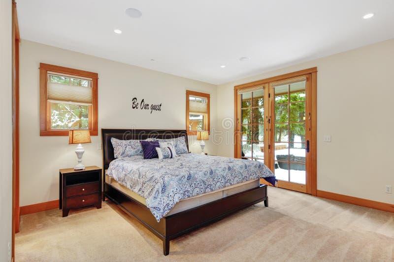 Interior agradável do quarto de hóspedes com as portas de vidro para suportar o pátio foto de stock royalty free