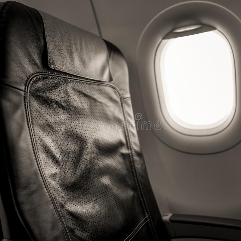 Interior of aircraft with empty seats and sunlight at the window. Travel concept. Black and white stock image