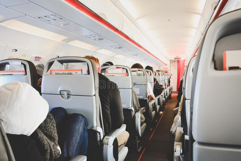 Interior of airplane in economy class with passengers sitting on seats, low cost airline, travel concept royalty free stock image