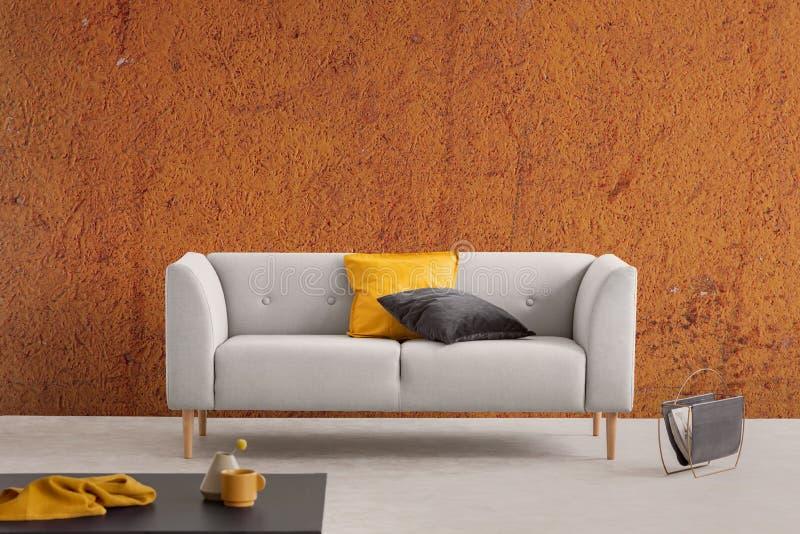 Interior anaranjado quemado de la sala de estar del sabi del wabi con el sofá gris con las almohadas y el estante de periódico am imagenes de archivo
