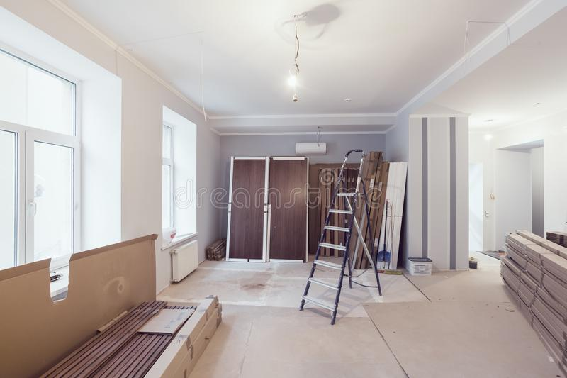 Interior of apartment during construction, remodeling, renovation, extension, restoration and reconstruction - ladde. R and construction materials in the room stock image