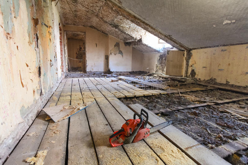 Interior of apartment during on the renovation and construction. Chainsaw on partially dismantled wooden floor and sawdust.  stock photography