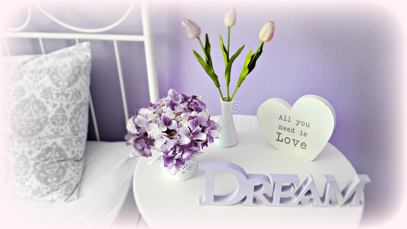 Interior arrangement on the bedside table: hydrangea, tulips and letters in purple tones. stock images