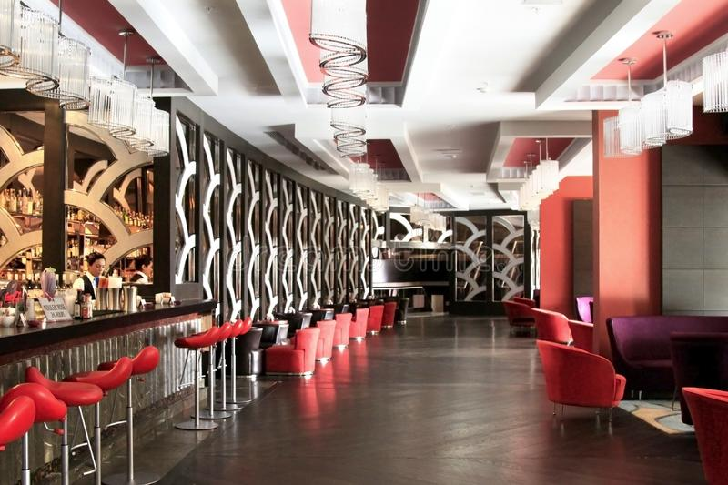 Interior of bar in high-tech style with high red bar stools and chairs. Parquet floor stock images