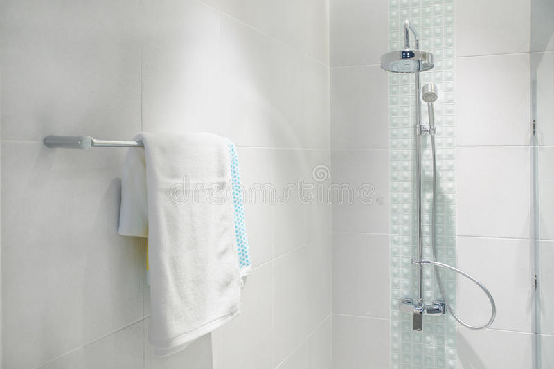 Interior of bathroom with modern shower head and white towel. At rail in bathroom royalty free stock images