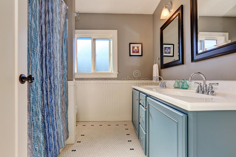 Interior of bathroom with vintage blue vanity cabinet and two sinks. Mocha walls with white plank paneled trim. Northwest, USA royalty free stock image