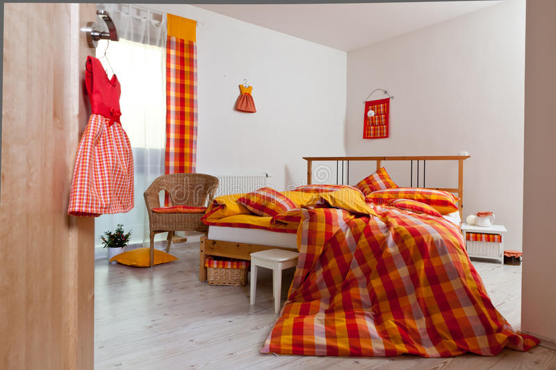 Interior of bedroom / Bedding in orange, yellow, red and white colours stock photography