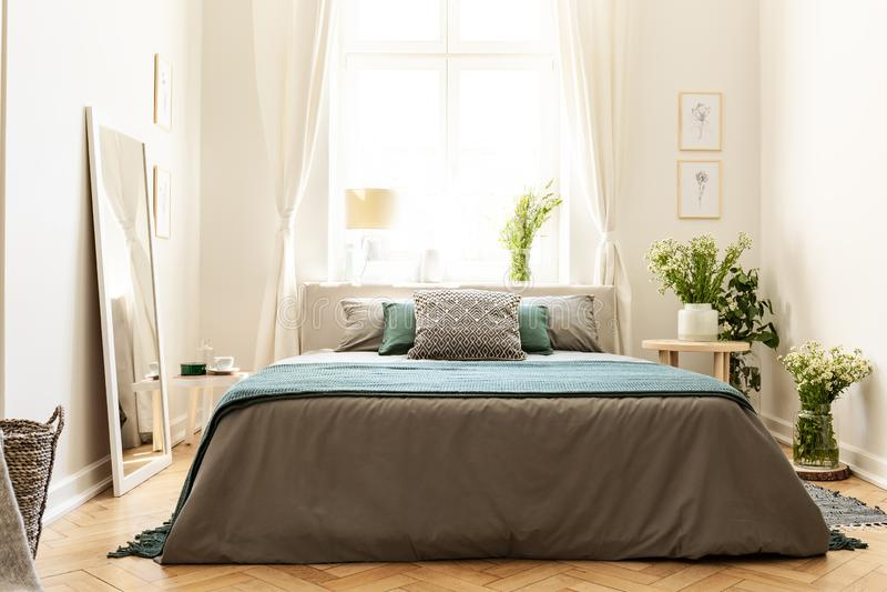 Interior bege, verde e cinzento do quarto em uma casa de cortiço com uma cama contra uma janela ensolarada e grupos de flores sel foto de stock
