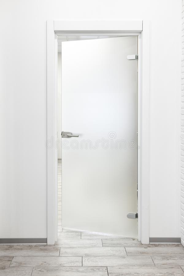 Interior blanco minimalista de la oficina con la puerta del vidrio esmerilado entornada imágenes de archivo libres de regalías