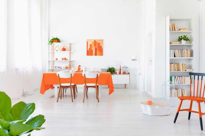 Interior blanco y de color naranja de la sala de estar en hogar moderno imagen de archivo libre de regalías