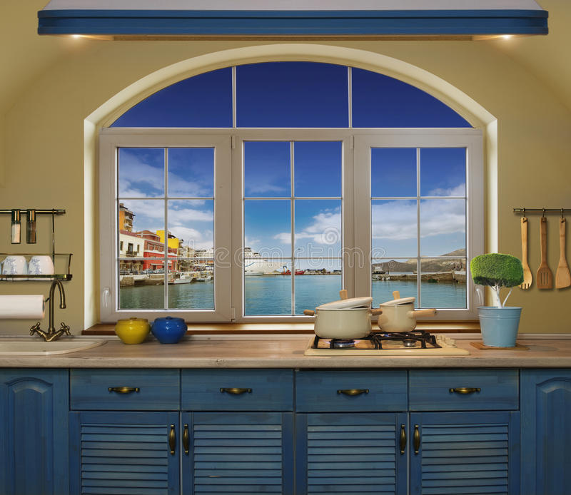Interior blue kitchen. Preparing lunch at home on the kitchen stove with a view from the window of the green meadows and fields stock photos