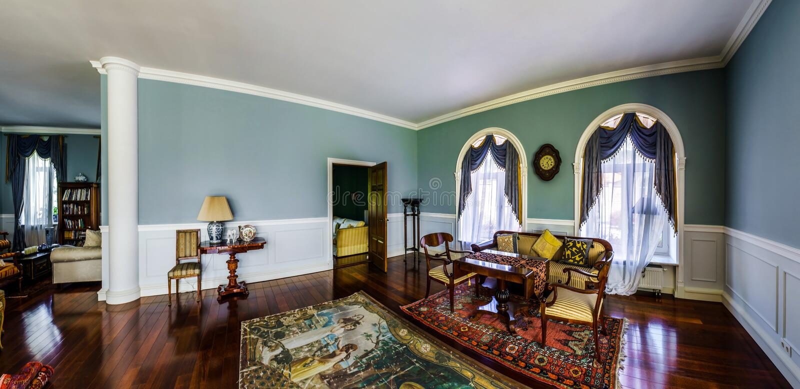 Interior bonito da sala de visitas com janelas altas imagem de stock