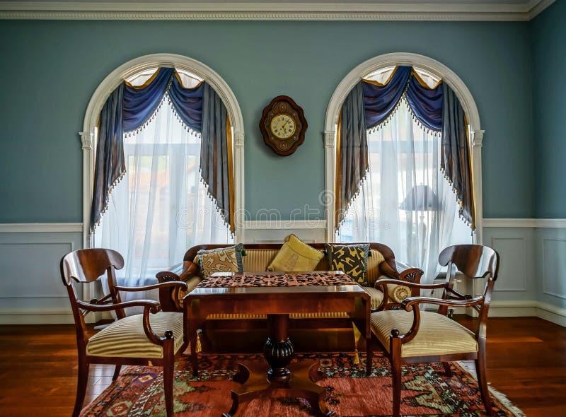 Interior bonito da sala de visitas com janelas altas imagens de stock