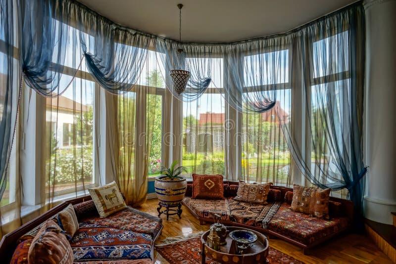 Interior bonito da sala de visitas com janelas altas fotos de stock