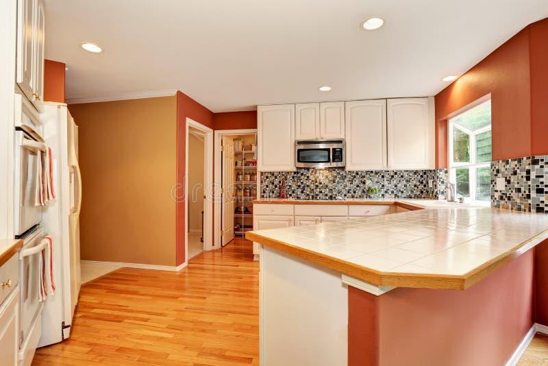 Interior branco da sala da cozinha com parte superior contrária da telha e assoalho de folhosa fotos de stock royalty free
