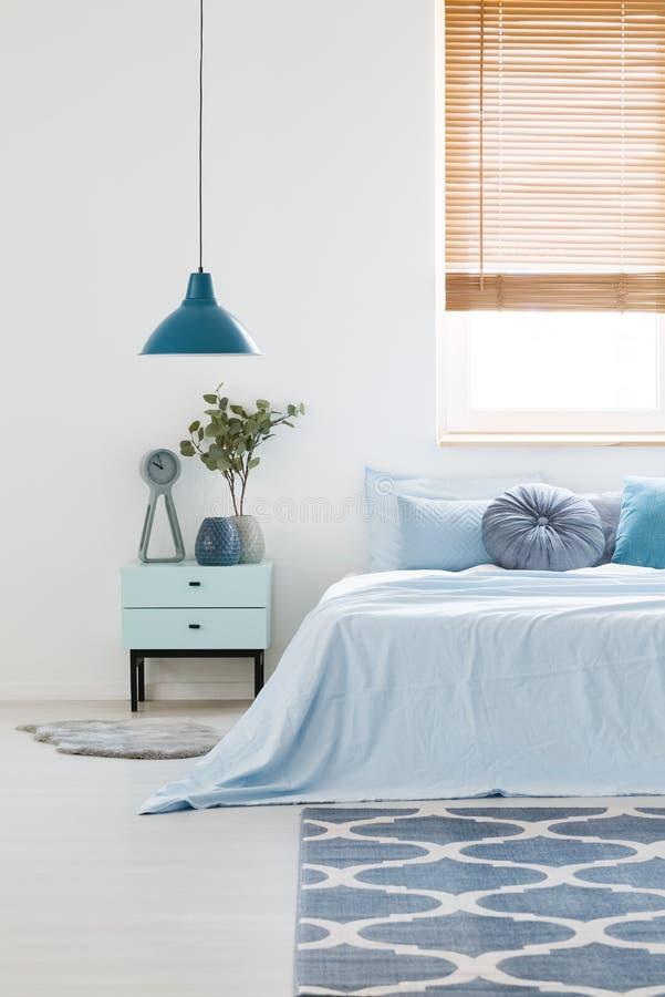 Interior branco do quarto com fundamento azul na cama de casal, lam da marinha imagens de stock