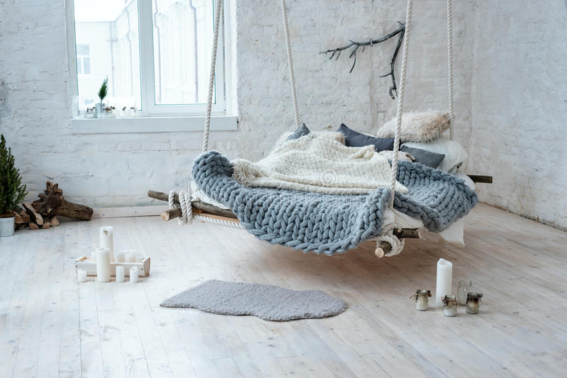 Interior branco do sótão no estilo escandinavo clássico Cama de suspensão suspendida do teto Grande manta cinzenta dobrada acolhe fotografia de stock