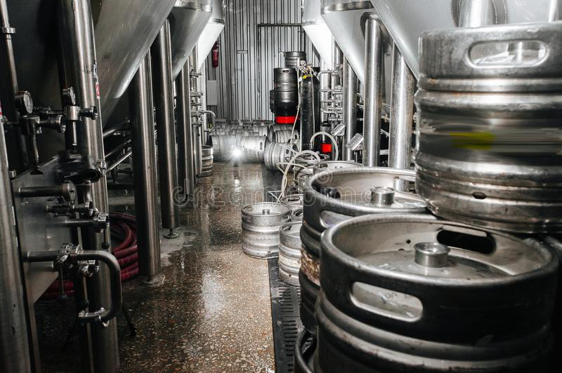 The interior of the brewery. Modern beer factory. Rows of steel. Stainless tanks for beer fermentation and maturation. Shop brewery. Geometry of plant stock photography