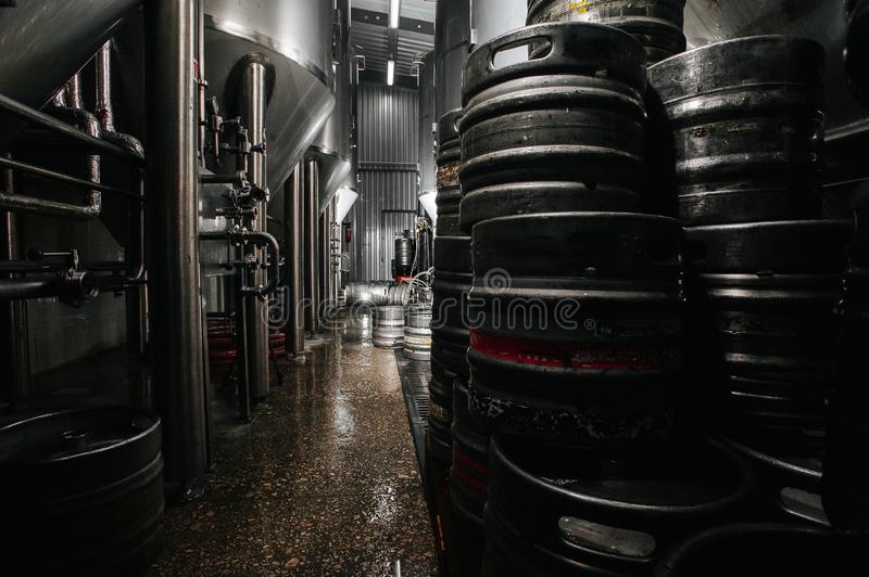 The interior of the brewery. Modern beer factory. Rows of steel. Stainless tanks for beer fermentation and maturation. Shop brewery. Geometry of plant royalty free stock photo