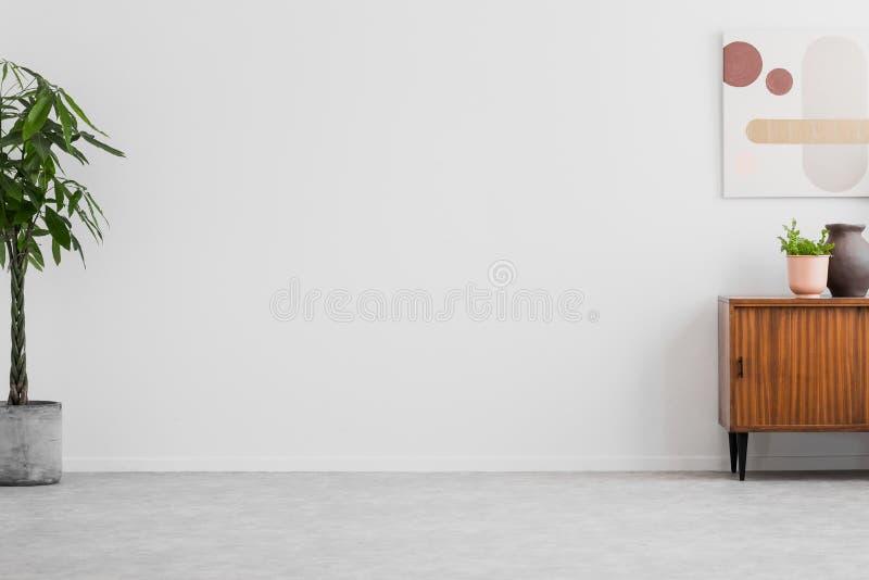 Interior brilhante da sala de visitas na foto real com plantas frescas, o armário retro e o cartaz simples Põe seu sofá aqui fotos de stock royalty free