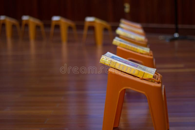 Interior of buddist temple called pagoda. Small plastic tables with praying books are staying in a lines on floor. stock image