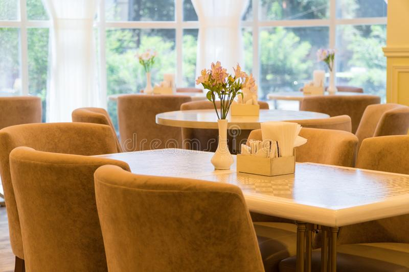 Interior of the cafe. Modern restaurant interior with windows and flowers. cafe room illuminated by sunlight stock photography