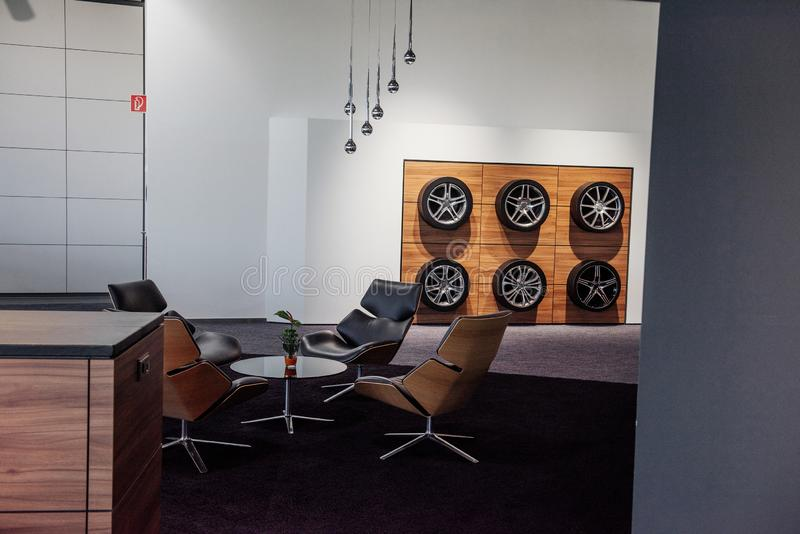 Interior of the car dealership with decorative wheels on the wall and four chairs with table at the center stock photos