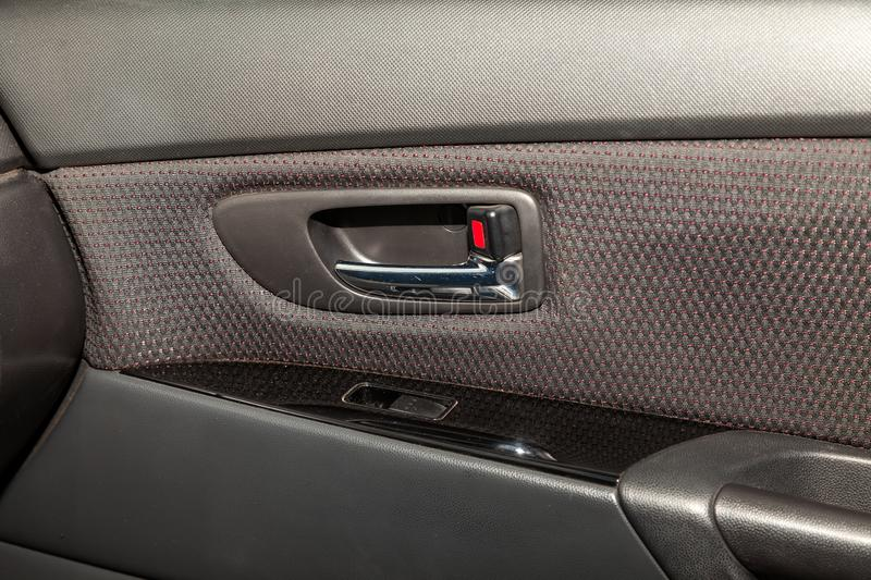 The interior of the car with a view of the passenger door with buttons, armrest and light gray leather after detailing and dry royalty free stock photography