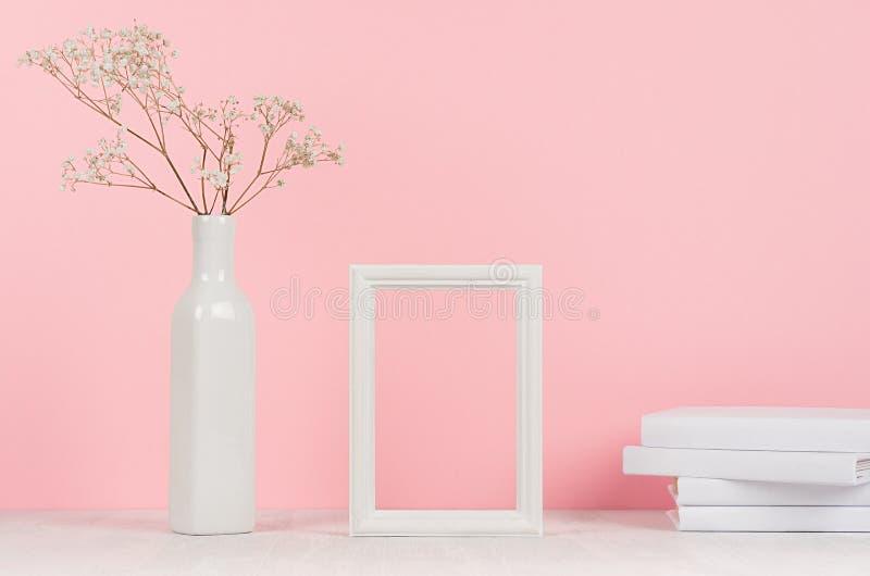 Interior casero de la elegancia de pequeñas flores secas en florero, los libros blancos y marco de madera en blanco de la foto en imagenes de archivo