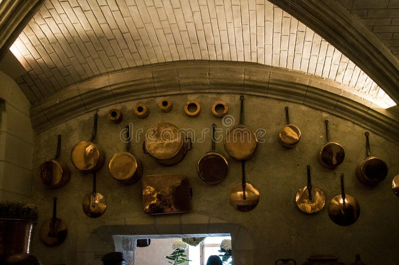 The interior of the Chenonceau castle. The cooking supplies hanging on the wall of the kitchen . royalty free stock photo