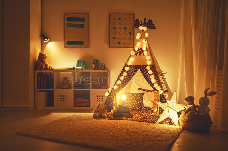 Interior of children`s playroom with tent, lamps and toys in dar stock photography