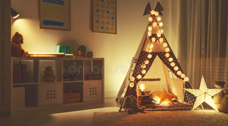 Interior of children`s playroom with tent, lamps and toys in dar stock photo