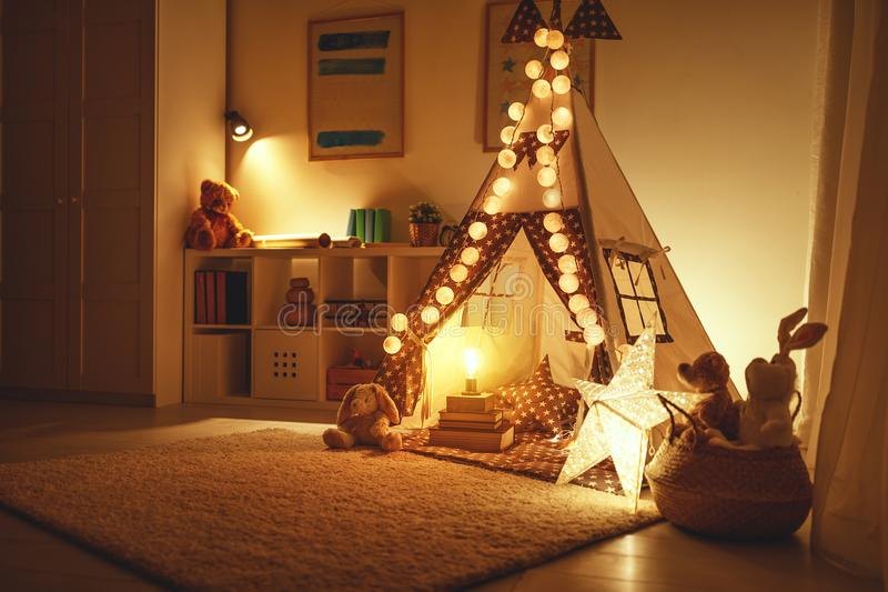 Interior of children`s playroom with tent, lamps and toys in dar. Interior of a children`s playroom with a tent, lamps and toys in dark stock image