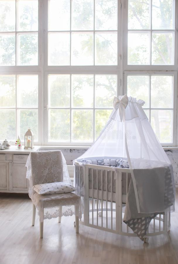 Interior of the children`s room, Provence style, oval baby cot, with canopy, light interior, large beautiful window royalty free stock photo