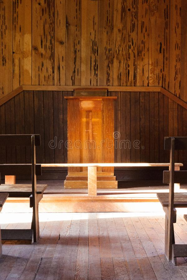 Interior of a Christian wooden church with a cross on the stand. An interior of a Christian wooden church with a cross on the stand in the countryside royalty free stock images