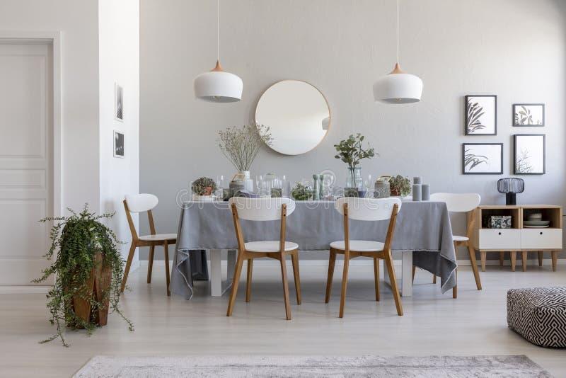 Interior cinzento da sala de jantar com uma tabela, as cadeiras e a planta fotos de stock
