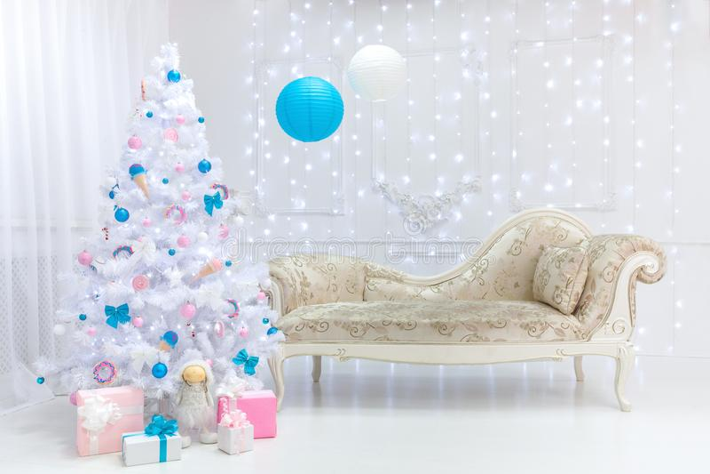 Interior clásico de la luz de la Navidad en los tonos blancos, rosados y azules con un sofá, un árbol y un moldeado imágenes de archivo libres de regalías