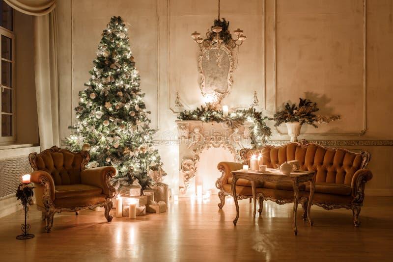 Interior clásico de un cuarto blanco con una chimenea adornada, sofá, árbol de navidad, guirnaldas, velas, linternas, regalos imagenes de archivo