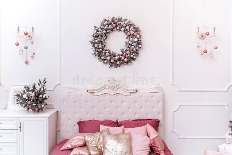 Interior clássico do quarto no estilo de ano novo Grinalda do Natal sobre a cama fotos de stock royalty free