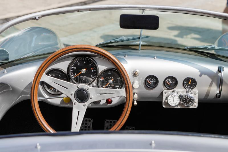 Interior of a classic oldtimer luxury sports car. Detailed photo of the interior dashboard, steering wheel and speedometer of a classic oldtimer sports car stock photography