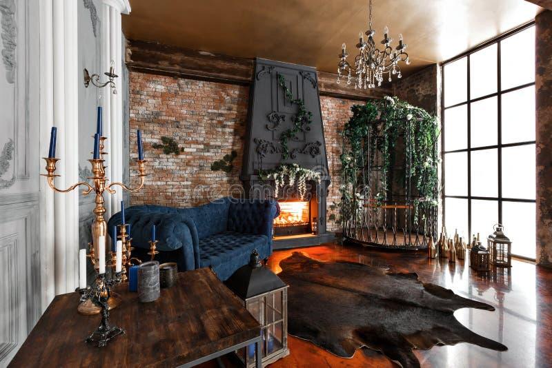 Interior com chaminé, velas, pele das vacas, parede de tijolo, a grande janela e uma pilha do metal de um sótão, sala de visitas, imagens de stock